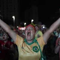 熱気はスタジアムの外にも…。ブラジルの先制ゴールを喜ぶファン=AP