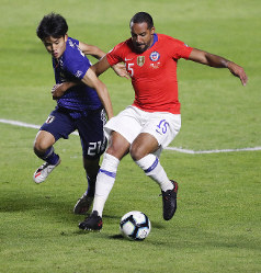 Japan's Takefusa Kubo, left, and Chile's Jean Beausejour, compete for the ball during a Copa America Group C soccer match at the Morumbi stadium in Sao Paulo, Brazil, June 17, 2019. (AP Photo/Nelson Antoine)