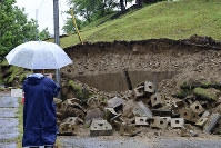 A person is seen taking a picture of a slope damaged by a powerful temblor, in Murakami, Niigata Prefecture, on the morning of June 19, 2019. (Mainichi/Kaho Kitayama)