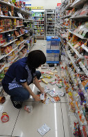 A store employee picks up items that fell off the shelves due to a strong jolt, at a Lawson convenience store in Tsuruoka, Yamagata Prefecture, on the night of June 18, 2019. (Mainichi/Rika Chonan)