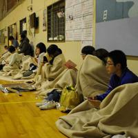 高台にある旧鶴岡市立由良小に避難し、毛布にくるまるなどする住民ら=山形県鶴岡市由良で2019年6月18日、長南里香撮影