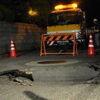 マンホールの周囲が陥没した道路=山形県鶴岡市城北町で2019年6月19日午前0時半過ぎごろ、長南里香撮影