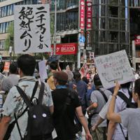 「二千万とか絶対ムリ」「年金払え!」などのプラカードを掲げて訴え行進するデモ参加者=東京・数寄屋橋交差点で2019年6月16日午後2時19分、山下浩一撮影