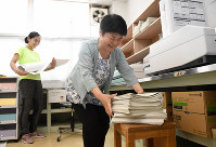 A staffroom administrative assistant, right, is seen working at a junior high school in Yokohama on June 19, 2019. She deals with a wide range of office duties, including making copies, answering the phone, greeting guests and hanging posters around the school. (Mainichi/Kimi Takeuchi)