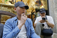In this June 17, 2019, photo, Joshua Ni, 24, and Fritz Ramirez, 23, vape from electronic cigarettes in San Francisco. (AP Photo/Samantha Maldonado)