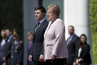 German Chancellor Angela Merkel, right, and Ukrainian President Volodymyr Zelenskiy, left, listen to the national anthems during the welcoming ceremony, prior to a meeting at the chancellery in Berlin, Germany, on June 18, 2019. (AP Photo/Markus Schreiber)