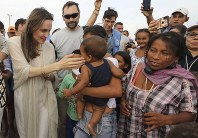 UNHCR's special envoy Angelina Jolie caresses a baby as she meets Venezuelan migrants at a United Nations-run camp in Maicao, Colombia, on border with Venezuela, on June 8, 2019. (AP Photo/Fernando Vergara)