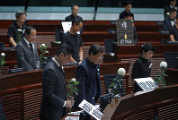 Pro-democracy lawmakers pay a silent tribute to the man who fell to his death on Saturday evening after hanging a protest banner on scaffolding on a shopping mall at the Legislative Council in Hong Kong, on June 19, 2019. (AP Photo/Vincent Yu)