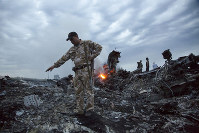 In this July 17, 2014 file photo, people walk amongst the debris at the crash site of a passenger plane near the village of Grabovo, Ukraine. (AP Photo/Dmitry Lovetsky)