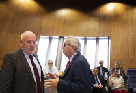 European Commission President Jean-Claude Juncker, right, speaks with European Commission Vice-President Frans Timmermans during a weekly meeting of EU commissioners at EU headquarters in Brussels, on June 18, 2019. (AP Photo/Virginia Mayo)