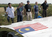 In this July 23, 2014 file photo, Malaysian investigators, along with members of the OSCE mission in Ukraine, examine a piece of the crashed Malaysia Airlines Flight 17 in the village of Petropavlivka, Donetsk region, eastern Ukraine. (AP Photo/Dmitry Lovetsky)
