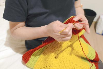 グループホームで趣味の編み物をする佐藤由美=宮城県内で