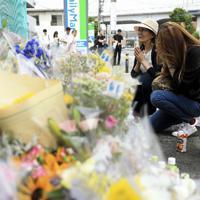 児童らが死傷した現場で手を合わせる人たち=川崎市多摩区で4日、玉城達郎撮影