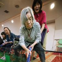 体を乗り出し、真剣な表情でプレーをする女性=大阪府豊中市で、梅田麻衣子撮影