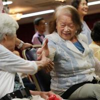 試合に勝ち、握手をする女性=大阪府豊中市で、梅田麻衣子撮影