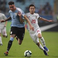 サッカー南米選手権【日本-ウルグアイ】前半、ウルグアイのヒメネスと競り合う日本の安部=ブラジル・ポルトアレグレで2019年6月20日、AP