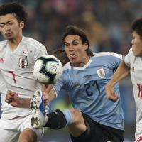 サッカー南米選手権【日本-ウルグアイ】前半、ウルグアイのカバーニをマークする日本の柴崎(左)と冨安=ブラジル・ポルトアレグレで2019年6月20日、AP