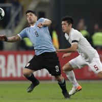 サッカー南米選手権【日本-ウルグアイ】後半、ゴールを狙うウルグアイのスアレス。右は日本の植田=ブラジル・ポルトアレグレで2019年6月20日、AP