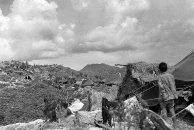 テントやかやぶきの小屋が建ち並ぶ大浦崎収容所=1945年7月撮影(沖縄県公文書館所蔵)