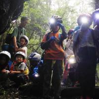 青木ケ原樹海にある火山洞窟を探検する子どもたち=山梨県内で2018年8月(ホールアース自然学校提供)