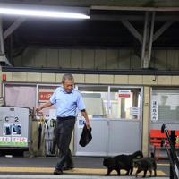 駅員さんのあとを歩くおさむとミニさむ(右)=2018年8月21日、おらが湊鉄道応援団提供