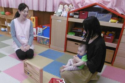 子どもをあやしながらスタッフと談笑する母親(右)=ドリーム子育て支援センター提供