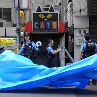 火災のあった個室ビデオ店の入り口(中央)をシートで覆う警察官=大阪市浪速区で2008年10月1日午前7時、小松雄介撮影