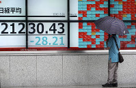 A man looks at an electronic stock board showing Japan's Nikkei 225 index at a securities firm in Tokyo, on June 24, 2019. (AP Photo/Eugene Hoshiko)