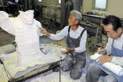 胸像の石こう取りをする鋳造家の寺沢啓治さん(左)と、作業を手伝う造形家の桐井雅康さん=愛知県犬山市栗栖垣之内で