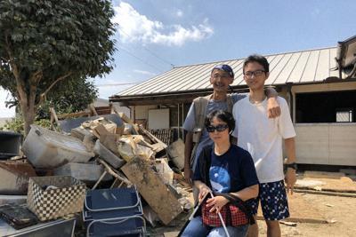 屋根まで浸水した真備町地区の自宅を取り壊す時に撮った山崎克枝さん一家の「記念写真」。長男(右)は2019年春、関東の大学に無事進学した=岡山県倉敷市で18年7月、山崎さん提供