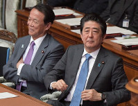 Prime Minister Shinzo Abe, right, and Deputy Prime Minister Taro Aso react to a speech by opposition Constitutional Democratic Party of Japan leader Yukio Edano during a House of Representatives plenary session on June 25, 2019. Edano was speaking in favor of a no-confidence motion against Abe's Cabinet. (Mainichi/Masahiro Kawata)