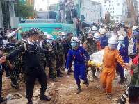 In this photo provided by Preah Sihanouk Provincial Authority, rescuers carry the body of a victim at the site of a collapsed building on June 24, 2019, in Preah Sihanouk province, Cambodia. (Preah Sihanouk Provincial Authority via AP)