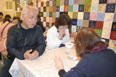 自慢の伝統食「オハウ」を振る舞いながら、来場者と談笑する山丸和幸代表(左)=北海道白老町本町で