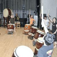 アート・リーさん(奥中央)と息を合わせて太鼓を打つ外国人の参加者ら=長野県飯田市吾妻町の市公民館で