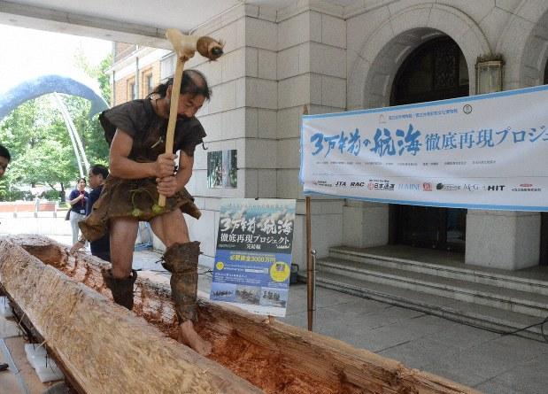 鹿と熊の皮で自作した「縄文人風の服」を来て丸木舟の作製を実演する、大工の雨宮国広さん=東京都台東区の国立科学博物館前で2018年7月31日、荒木涼子撮影
