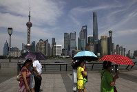 In this file photo taken on May 22, 2015, people walk on the Bund against buildings in Pudong, China's financial and commercial hub, in Shanghai. (AP Photo/Paul Traynor)
