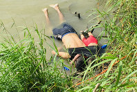 The bodies of Salvadoran migrant Oscar Alberto Martinez Ramirez and his nearly 2-year-old daughter Valeria lie on the bank of the Rio Grande in Matamoros, Mexico, on June 24, 2019, after they drowned trying to cross the river to Brownsville, Texas. (AP Photo/Julia Le Duc)