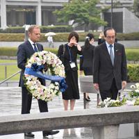 花輪を持ち、献花台に向かう欧州理事会のドナルド・トゥスク常任議長(左)=広島市中区中島町の平和記念公園で、小山美砂撮影