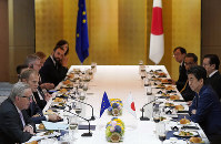 European Commission President Jean-Claude Juncker, left, and European Council President Donald Tusk, second left, sit at the table with Japanese Prime Minister Shinzo Abe, right, at the start of their working lunch on the sidelines of the G20 Summit at the International Exhibition Center in Osaka, Japan, on June 27, 2019. (Franck Robichon/Pool Photo via AP)