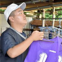 洗濯したビブスを干すマネジャーの小祝陽祐さん(3年)=常陸太田市の太田第一高グラウンドで