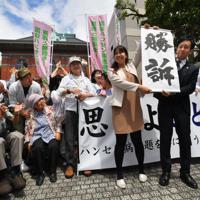 支援者の前で「勝訴」の紙を掲げる原告の弁護士=熊本市の熊本地裁前で2019年6月28日午後2時2分、田鍋公也撮影