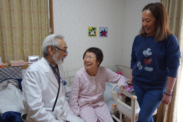 訪問診療で80代女性に「調子はどうですか?」と語りかける高林克日己さん=千葉県松戸市で2019年3月25日、中村好見撮影