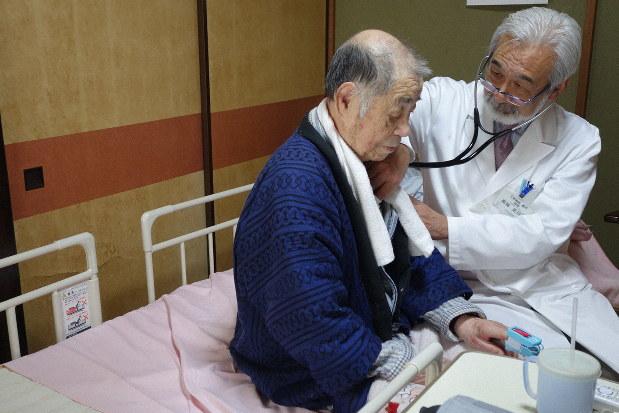 訪問診療で80代男性の胸に聴診器を当てる高林さん