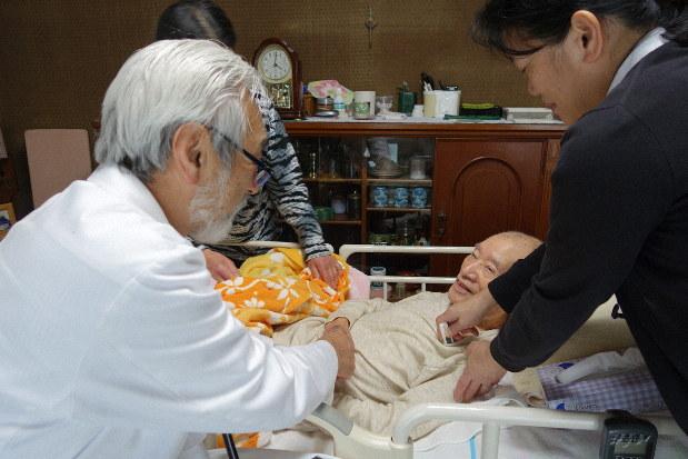 訪問診療した90代男性の手を握る高林さん