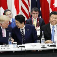 G20サミットで行われたデジタル経済に関する首脳特別イベントを終え、トランプ米大統領(左)と握手を交わす安倍首相。右は中国の習近平国家主席=大阪市で2019年6月28日午後0時25分(代表撮影)