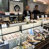 専務の太田新太郎さん(右)と、父で4代目社長の等さん。さまざまな和菓子がショーケースを彩る=いずれも新潟市中央区で