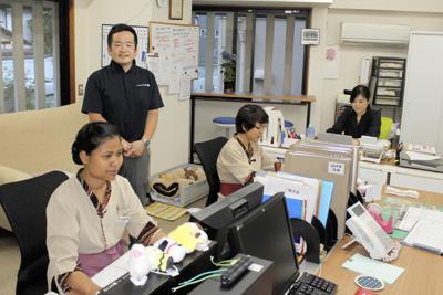 改修した「小松家・八の坊」のフロントと望月敬太専務(左奥)。パソコンで仕事するのはネパール人のチャウダリ・ビスヌさん(手前)ら=静岡県伊豆の国市長岡で