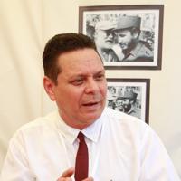 インタビューに応じるソムリエのオーランドさん。壁にはフィデル・カストロと談笑するヘミングウェーの写真が飾られている=ハバナ市内で2019年5月8日、竹下理子撮影