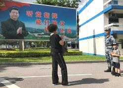 習近平国家主席の写真をあしらった看板の前で、兵士と共に記念撮影する家族連れ=香港・石崗基地で2019年6月29日午前9時13分、福岡静哉撮影