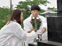 Daichi Obata and his mother Akemi are seen placing flowers on the grave of his father Kazuhiko, in their hometown of Futaba, Fukushima Prefecture, on June 29, 2019. (Mainichi/Tatsushi Inui)